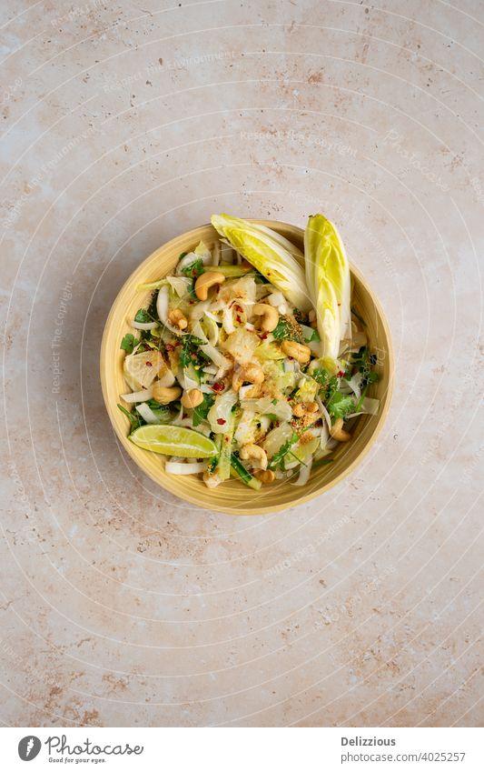 Draufsicht auf einen köstlichen veganen Pomelo-Salat nach Bali-Art mit Chicorée, Gurke, Cashewnüssen, Koriander , gerösteter Kokosnuss und Chill-Limetten-Dressing, Platz kopieren