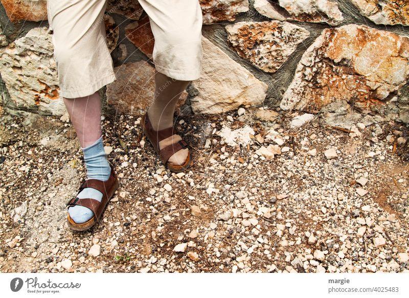 Ein Mann trägt Sandalen mit unterschiedlichen Socken Mode Beine Fuß Außenaufnahme Mauer steinig Schuhe Kuriosität steiniger weg Mensch Hose Erwachsene Tag