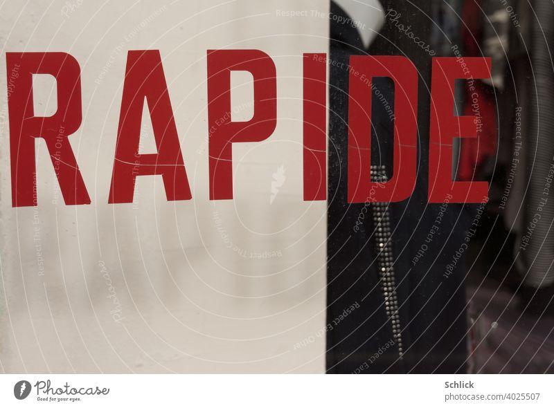 """""""RAPIDE"""" steht in französischer Sprache auf einem Schaufenster in roten Großbuchstaben geschrieben und wirft seinen Schlagschatten """"RAPID"""" ins Deutsche übersetzt auf einen weißen Hintergrund"""