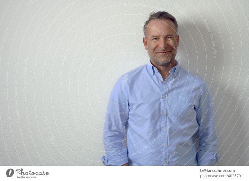 Gut aussehender, unrasierter, reifer Mann in blauem Hemd, der an einer weißen Wand steht und mit freundlichem Lächeln in die Kamera schaut. Brustbild in halber Länge mit Kopierraum
