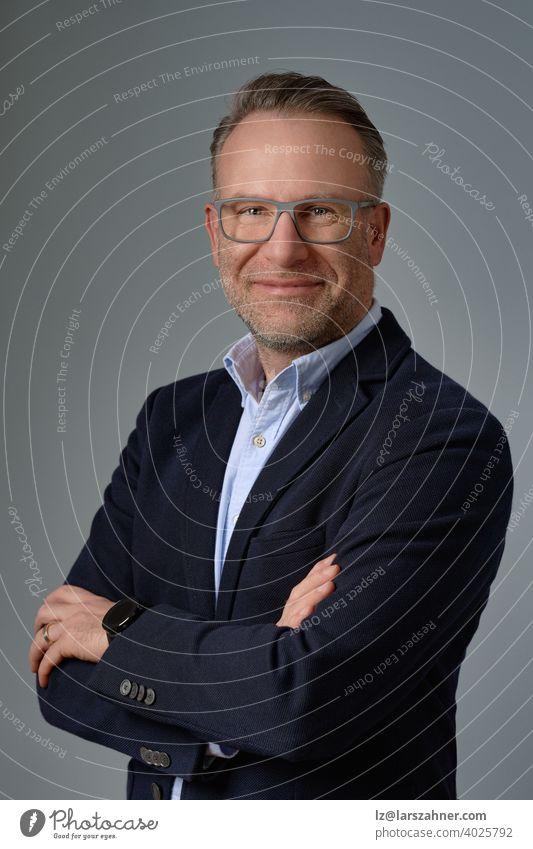 Lächelnder reifer Geschäftsmann mit Brille, im Anzug ohne Krawatte, steht vor grauem Hintergrund und posiert mit verschränkten Armen vor der Kamera. Studio-Porträt in halber Länge mit halber Drehung
