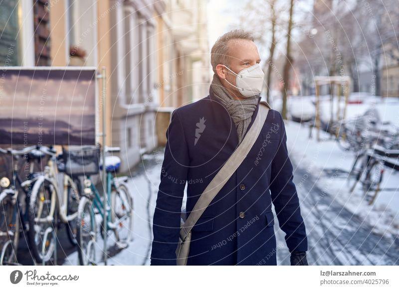 Mann mit einer schützenden chirurgischen Gesichtsmaske während der Covid-19- oder Coronavirus-Pandemie und Wintermantel mit Ledertasche über der Schulter, der eine verschneite städtische Straße mit geparkten Fahrrädern in Nahaufnahme entlanggeht und zur Seite schaut