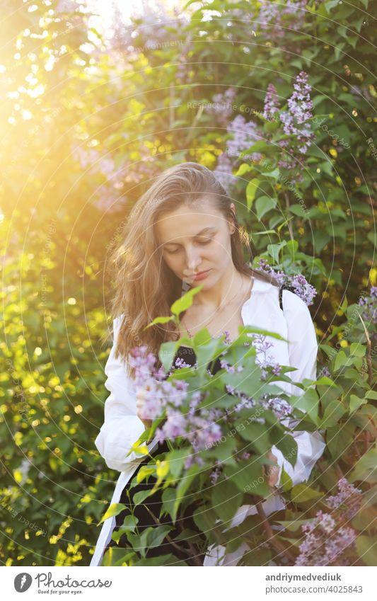 unwirklich schöne junge Frau zu Fuß in einem grünen blühte im Frühjahr in einem Lavendelgarten mit einem Blumenstrauß von Flieder in den Händen. Closeup Mode romantisches Porträt. riechen die Blumen
