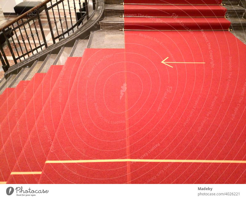Roter Teppich mit gelbem Pfeil während Corona im Treppenhaus eines Museum in der Hauptstadt Berlin, Deutschland Läufer Hinweis Richrung Sicherheit