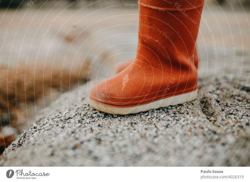 Kind rote Gummistiefel Fuß Schuhe Stiefel Regen Außenaufnahme nass Wetter Wasser dreckig Mensch Freude Beine Textfreiraum Farbfoto schlechtes Wetter Pfütze