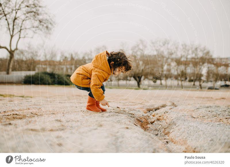 Seitenansicht eines Kindes mit roten Gummistiefeln beim Spielen im Freien Kindheit Freude Kindheitserinnerung Kleinkind Junge Fröhlichkeit Farbfoto Mensch