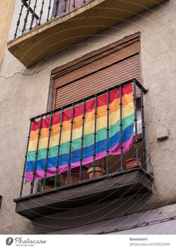 LGBT-Regenbogenflagge an einem Balkon an einer Hausfassade irgendwo in einer Altstadt in Südeuropa schwul lesbisch Homosexualität Liebe Freiheit Lifestyle Fahne