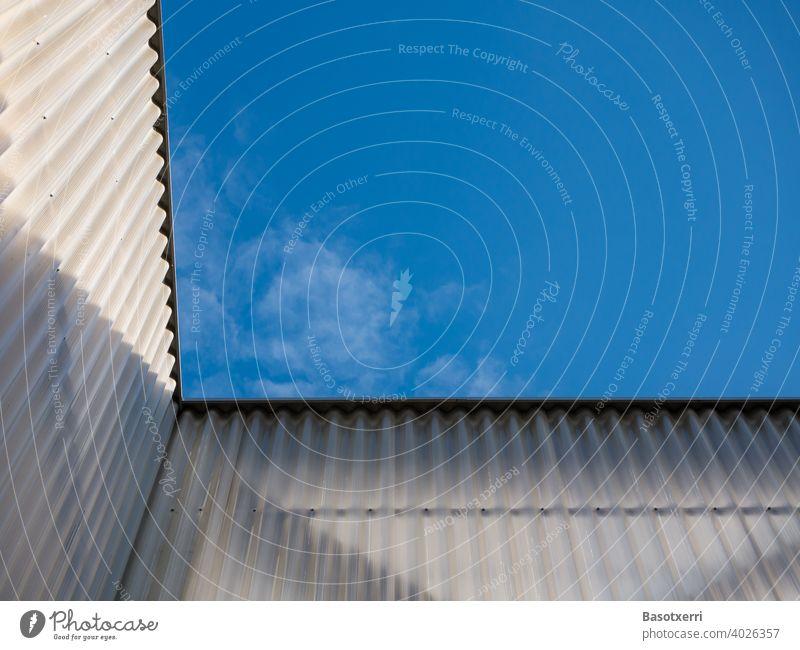 Blick in den blauen Himmel an einer modernen halbdurchsichtigen, gewellten Fassade Kunststoff sonnig Blauer Himmel Licht Schatten niemand Menschenleer Tag Sonne