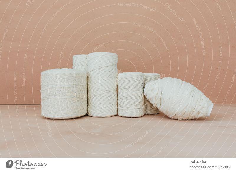 Satz von weißen Strickgarn Spule auf beige Hintergrund. Verschiedene Größe Baumwollfäden. stricken Baumwolle Garn Spulen Faser Nähen vereinzelt Schnur Handwerk