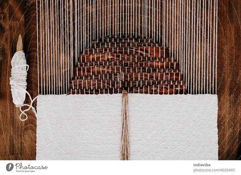Weberei-Projekt in Arbeit. Unfertiger handgefertigter Wandteppich auf einem Webstuhl. Natürliche Materialien, Kokosnussfaser und Baumwollseil. Seil Garn Faser