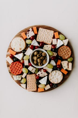 Käseteller mit verschiedenen Käsesorten. Camembert, Cheddar, Ziegenkäse, Bleu, Trauben und Oliven mit Crackern. Gesundes vegetarisches Essen Idee. Platte