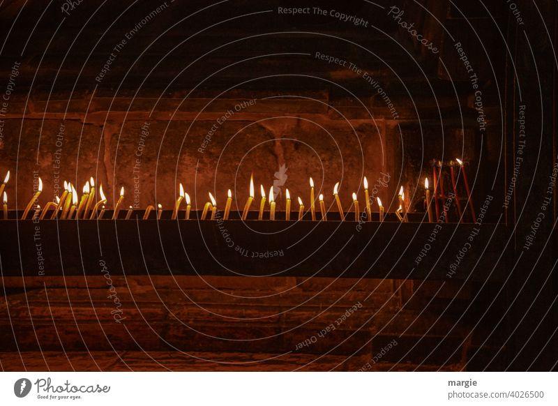 Viele brennende Kerzen in einer Kirche! Kerzenschein Kerzenflamme Menschenleer Flamme Licht Kerzendocht leuchten dunkel Feuer Wachs hell Romantik Wärme