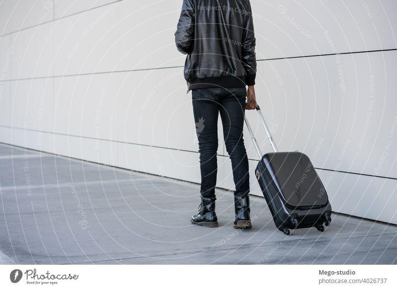 Tourist, der beim Spaziergang im Freien einen Koffer trägt. Reisen Mann Reisender Ausflugsziel Konzept Feiertag Tag Freude genießen Abenteuer Ferien Porträt