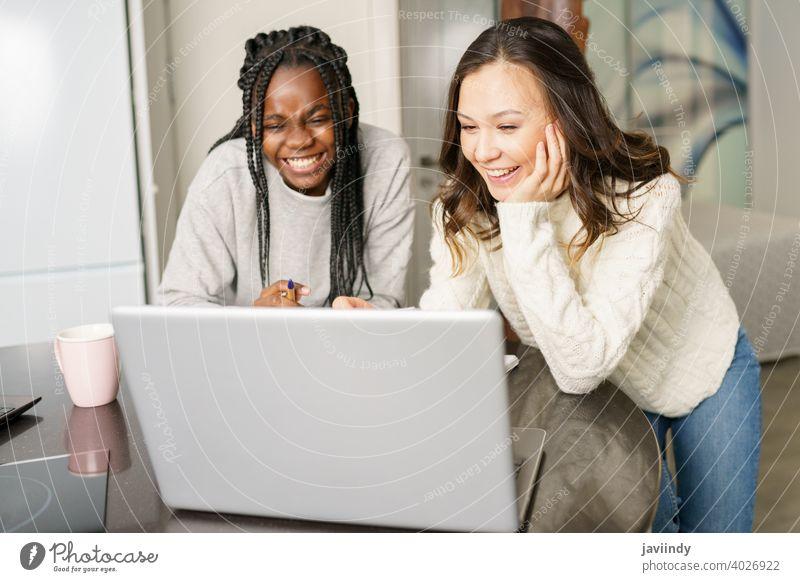 Zwei College-Mädchen studieren gemeinsam zu Hause mit Laptops beim Kaffeetrinken Schüler Frauen multiethnisch heimwärts Computer Hochschule studierend
