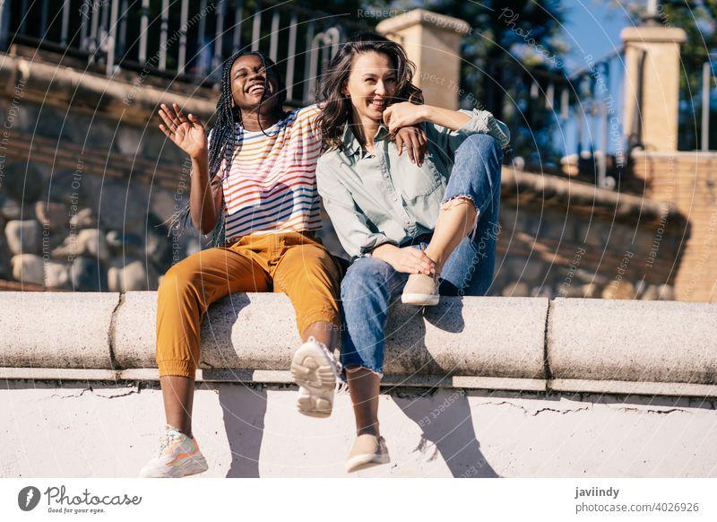 Zwei Freunde, die sich gemeinsam auf der Straße amüsieren und auf einer Stadtmauer sitzen. Frauen multiethnisch schwarz Afro-Look Mädchen Schüler zwei Spaß