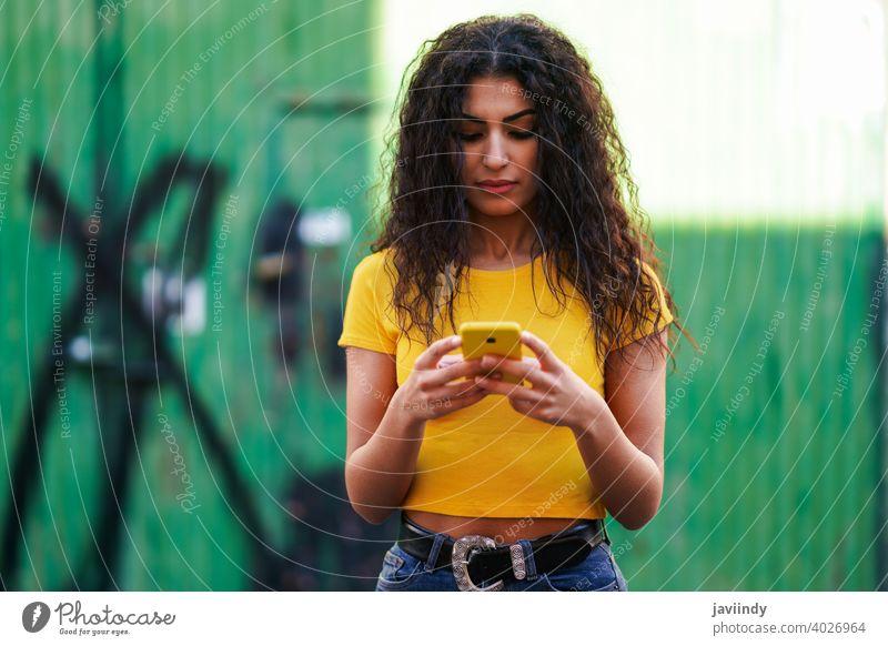Junge arabische Frau geht auf der Straße mit ihrem Smartphone jung Texten Nachricht Tippen gelb copyspace Mädchen Aufnahme Frisur attraktiv schön urban