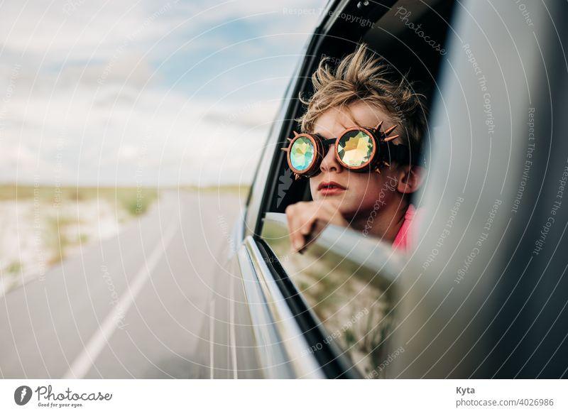 Ein Junge schaut mit einer Kaleidoskopbrille aus dem Fenster eines fahrenden Fahrzeugs Kaleidoskop-Schutzbrille Autoreise Ferien & Urlaub & Reisen