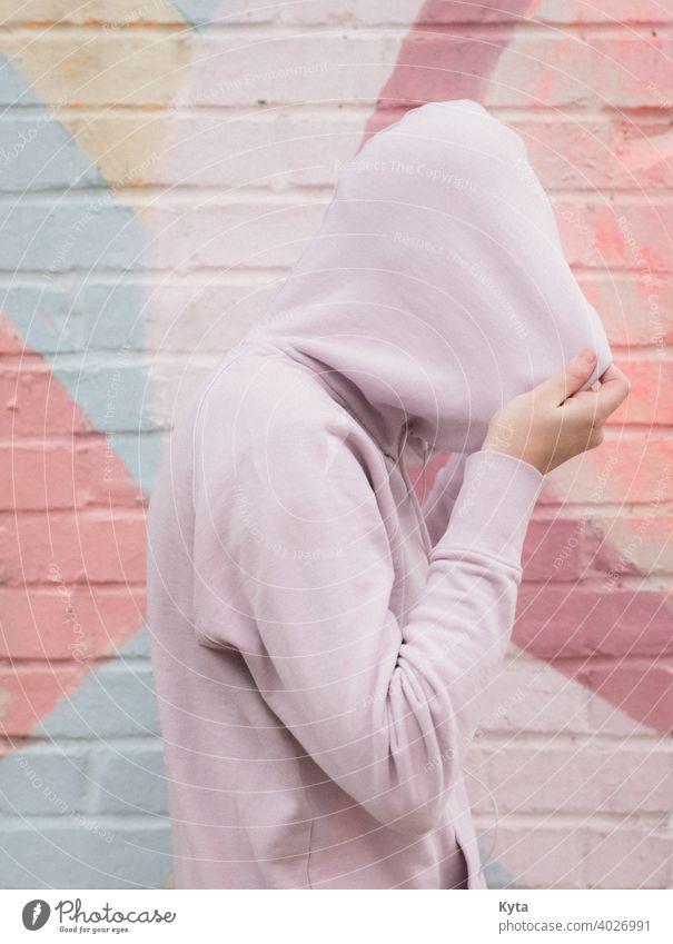 Introvertierter Teenager zieht sich den Kapuzenpulli über den Kopf introvertiert schüchtern Pastell Pastellton pastellfarbene Töne psychische Gesundheit