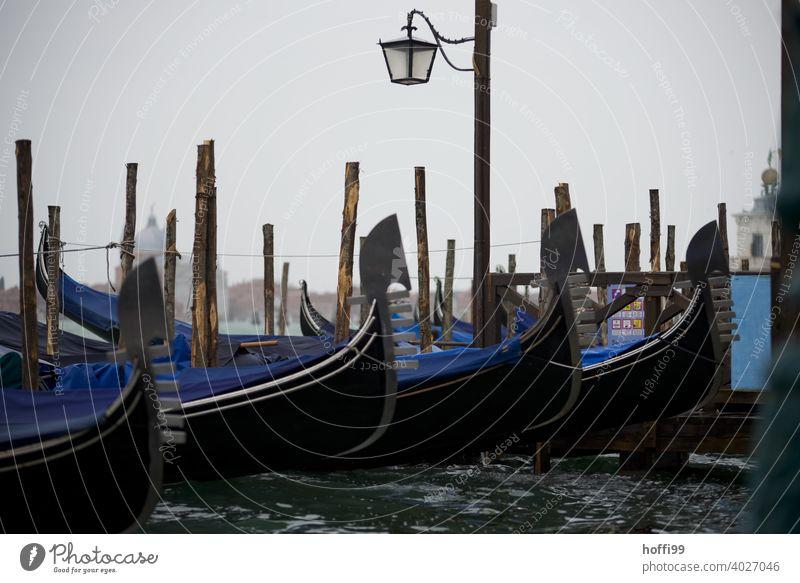 Blick im Regen auf einen Anlegeplatz von Gondeln in Venedig Lagune gondeln Gondoliere Wasser Wasserfahrzeug Italien Bootsfahrt Tourismus Hafenstadt Schifffahrt