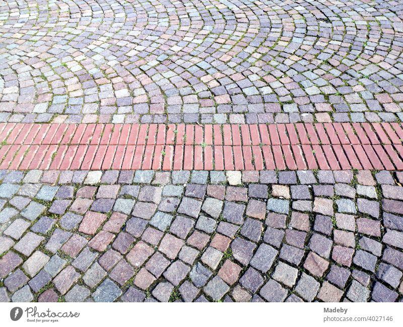 Rote Backsteine eingelassen in buntes Kopfsteinpflaster auf einem Platz in Bad Salzuflen bei Herford in Ostwestfalen-Lippe, Deutschland Pflaster Straßenpflaster