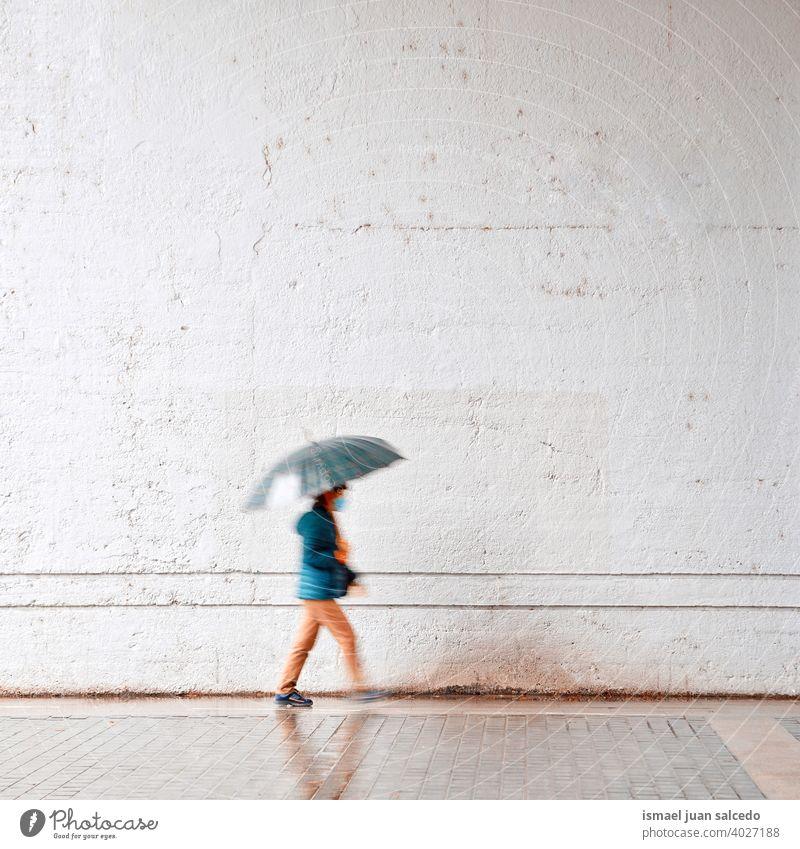 Frau mit einem Regenschirm in regnerischen Tagen im Frühling Saison Menschen Person regnet Regentag Wasser menschlich Fußgänger Straße Großstadt urban Bilbao