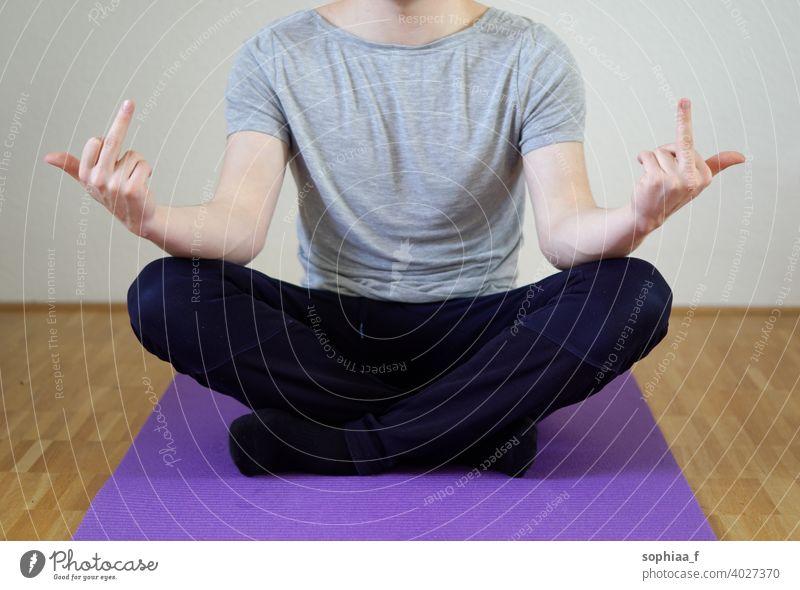 Stressbewältigung - Mann sitzt im Schneidersitz und zeigt beide Mittelfinger Meditation Work-Life-Balance ficken gestresst Yoga mit gekreuzten Beinen Burnout