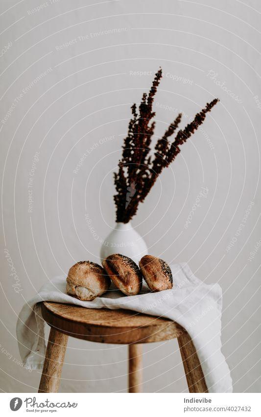 Drei Sauerteigbrötchen mit Mohn und Sesam auf einer Serviette auf einem Holzschemel, und getrocknete Wildblumen im Hintergrund Brötchen Frühstück Brot Gluten