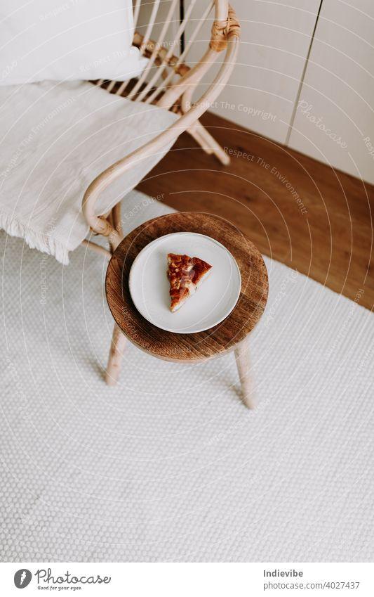Ein Stück hausgemachter Apfelkuchen auf einem Holzhocker im Wohnzimmer Pasteten Vanille Dessert Kuchen süß Scheibe Lebensmittel Frucht warm lecker geschmackvoll