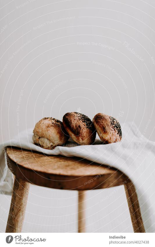 Drei Sauerteigbrötchen mit Mohn und Sesam auf einer Serviette auf einem Holzschemel Brötchen Frühstück Brot Gluten Gebäck Bäckerei frisch Morgen Mehl ganz