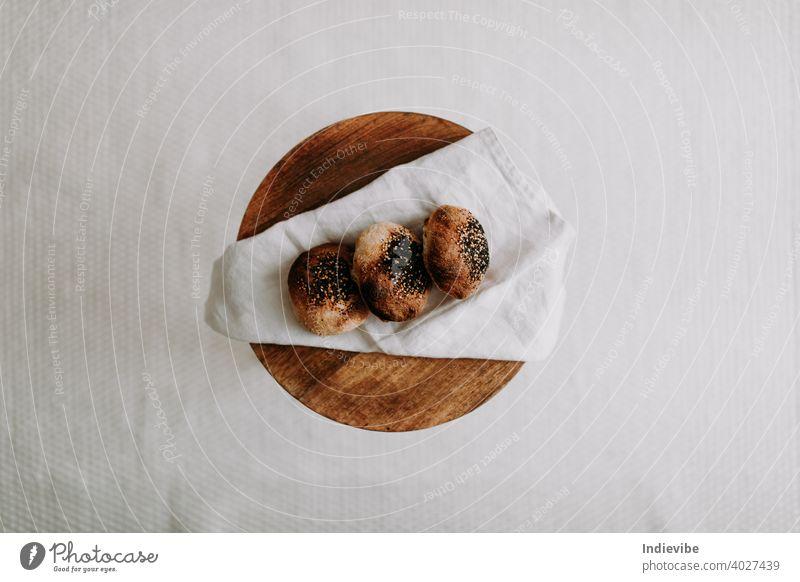 Drei Sauerteigbrötchen flachgelegt mit Mohn und Sesam auf einer Serviette auf einem Holzhocker Brötchen Frühstück Brot Gluten Gebäck Bäckerei frisch Morgen Mehl