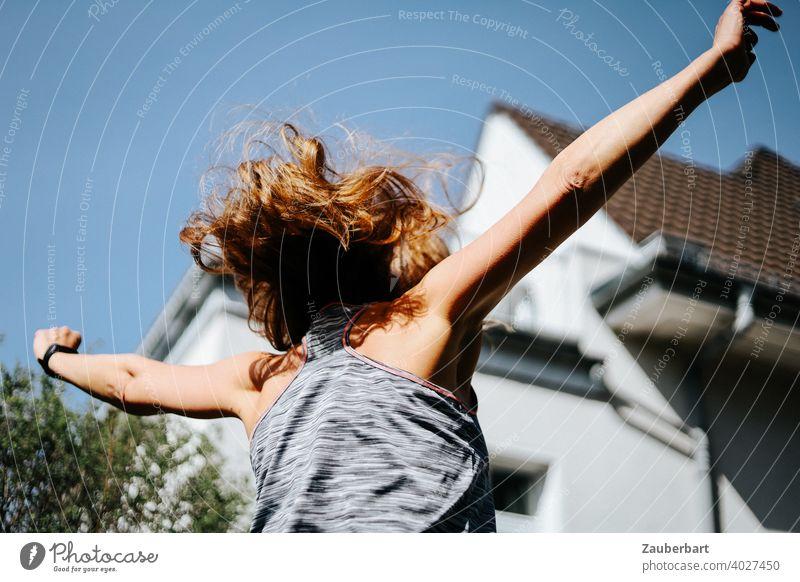 Frau mit wehenden Haaren springt lebendig mit erhobenen Armen junge Frau springen Frohsinn Lebensfreude Sport Sommer schön Freude Glück Energie hurra juchhu