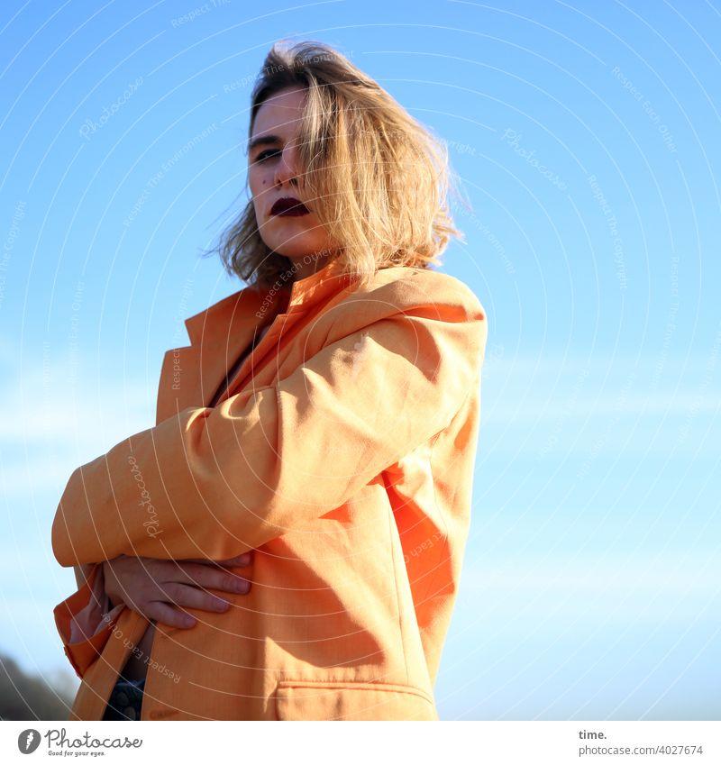 Lara frau jacke himmel hand schutz sonnig wolken stehen arme verschränken schatten frisur haare skeptisch beobachten scheu ärgerlich verärgert