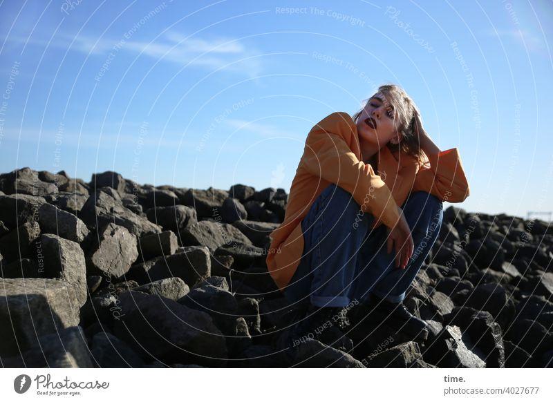 Lara frau jacke wellenbrecher steine himmel sitzen hand schutz sonnig jeans aufstützen abstützen wolken schatten