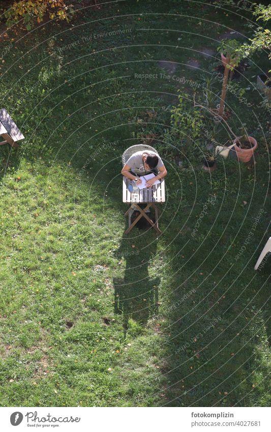 Vogelperspektive auf einen jungen Mann, der im Garten an einem kleinenTisch sitzt  und in ein Heft schreibt junger Mann Gartentisch lernen studieren schreiben