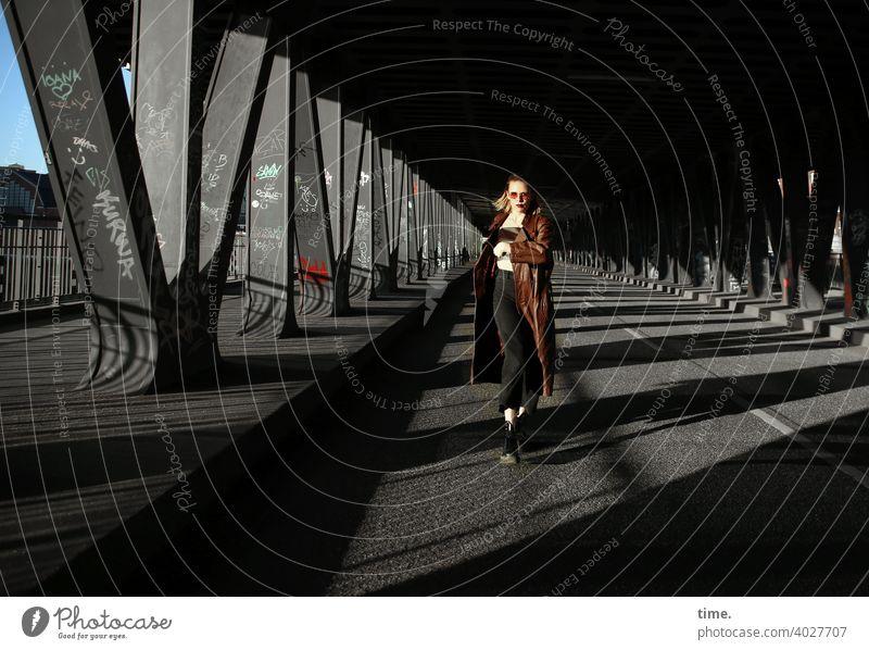 Lara rennt mantel ledermantel Frau sonnenbrille metall brücke sonnig schatten urban geheimnisvoll skeptisch Haare blond blick brückenpfeiler straße beobachten