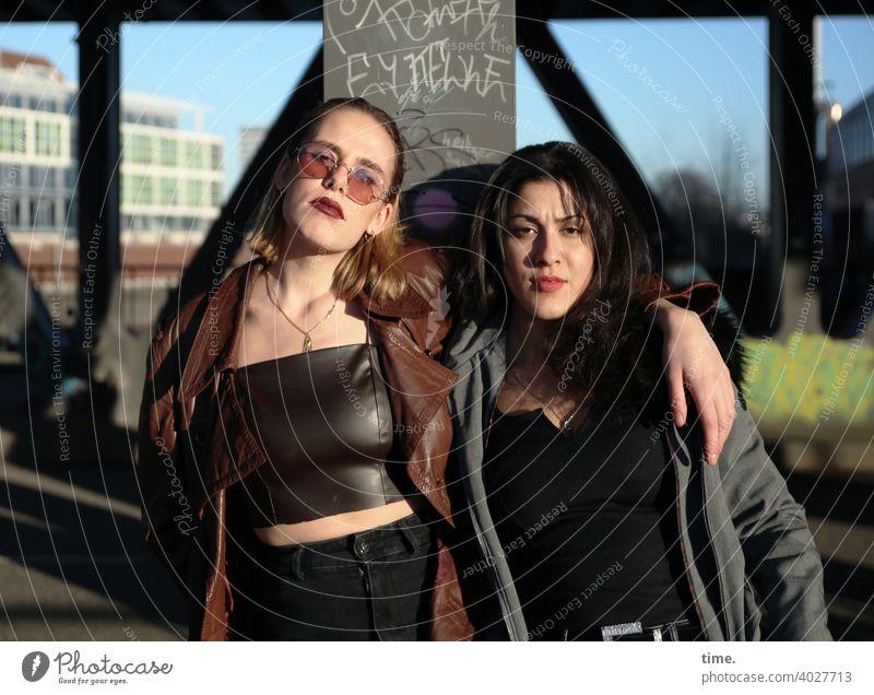 Lara und Estila frau langhaarig stehen ernst cool freundschaft mantel lässig blond dunkelhaarig architektur brücke sonnig sonnenlicht miteinander beieinander
