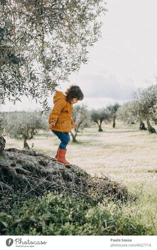 Kind spielt im Freien Klettern Spielen Natur orange rot authentisch Mädchen Baum Farbfoto Freizeit & Hobby Außenaufnahme Freude Spielplatz Mensch Kindheit Glück