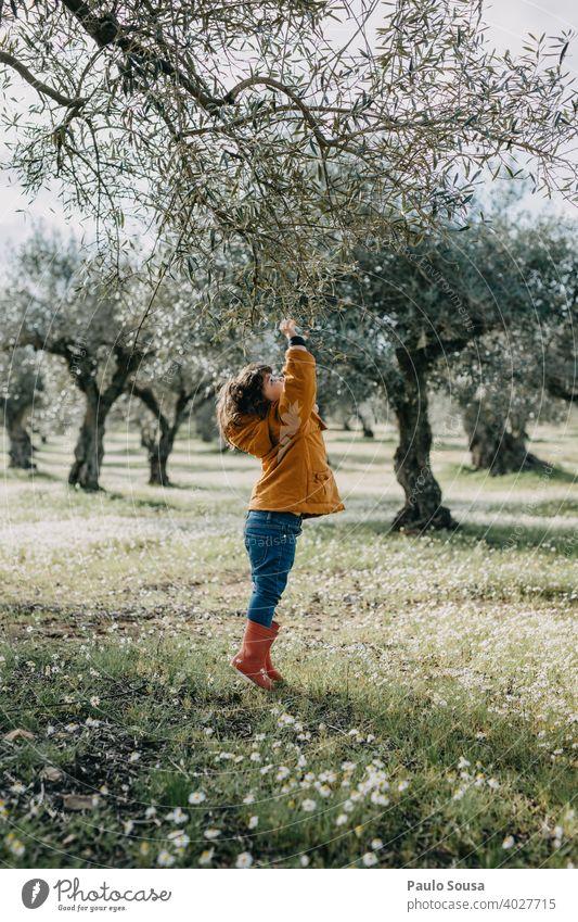 Kind mit roten Gummistiefeln spielt mit Baum Umwelt Natur Kindheit Frühling Mädchen Tag grün Farbfoto Außenaufnahme authentisch heiter Freude Pflanze jung Glück