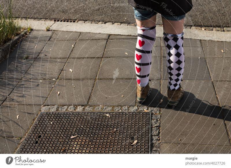 AST10 l Ein Mädchen trägt zwei unterschiedlich gemusterte Strümpfe mit roten Herzen und schwarzen Karos Strumpf Muster mustermix kurze hose Schuhe Wanderschuhe