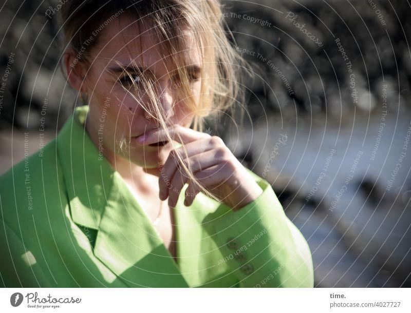 Lara Frau blick blond Haare nachdenklich jacke grün neongrün hand steine ufer wasser