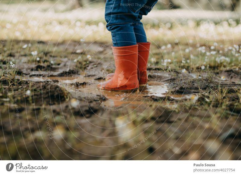 Kind mit roten Gummistiefeln spielt auf einer Pfütze Kindheit Wetter Mensch Wasser Spielen Stiefel Freude nass Regen authentisch Herbst Frühling Winter