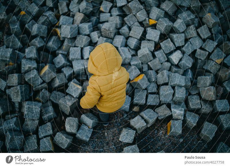Kleinkind spielt mit Steinen erkunden gelb Kind Rückansicht Kindheit Außenaufnahme Natur Farbfoto Freizeit & Hobby Abenteuer Tag Mensch Junge Spielen 1