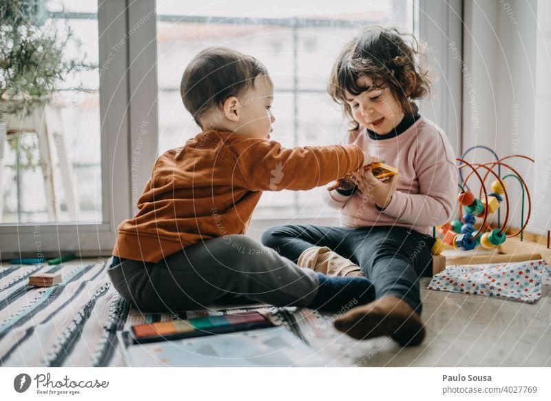 Bruder und Schwester spielen auf dem Boden Geschwister Familie & Verwandtschaft Kind Kindheit authentisch Kaukasier Gefühle Kleinkind Spielen Lifestyle