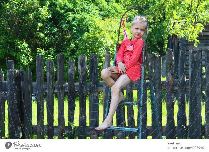 Barfuß Sommer auf dem Dorf. Porträt eines kleinen Mädchens mit blonden Haaren in einem roten Kleid, das auf einer Trittleiter auf dem Lande vor dem Hintergrund eines alten Holzzauns und grünem Laub an einem sonnigen Sommertag sitzt.