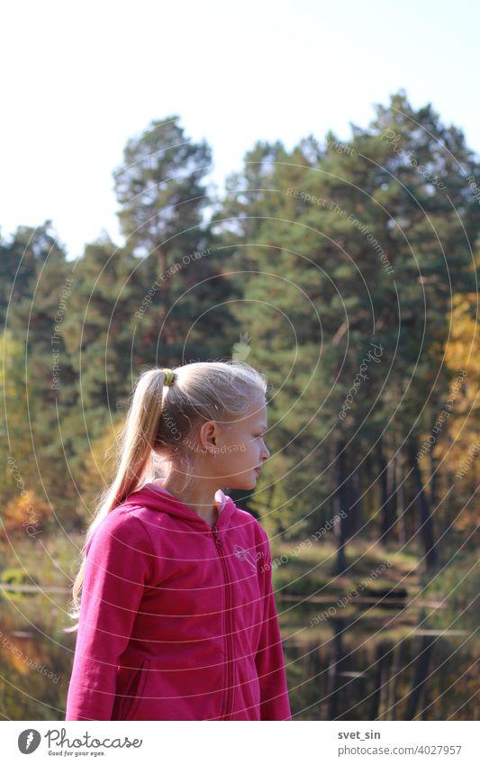 Ein Teenager-Mädchen mit langen blonden Haaren steht am Ufer eines Sees vor dem Hintergrund von Wasser und herbstlich gelbem Wald im Herbstsonnenlicht. Porträt eines blonden Mädchens im Profil.