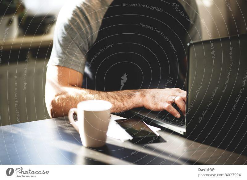 Mann sitzt an einem Tisch am Laptop und tippt mit den Finger auf der Tastatur Notebook tippen Internet digital Tippen modern Technik & Technologie Homeoffice