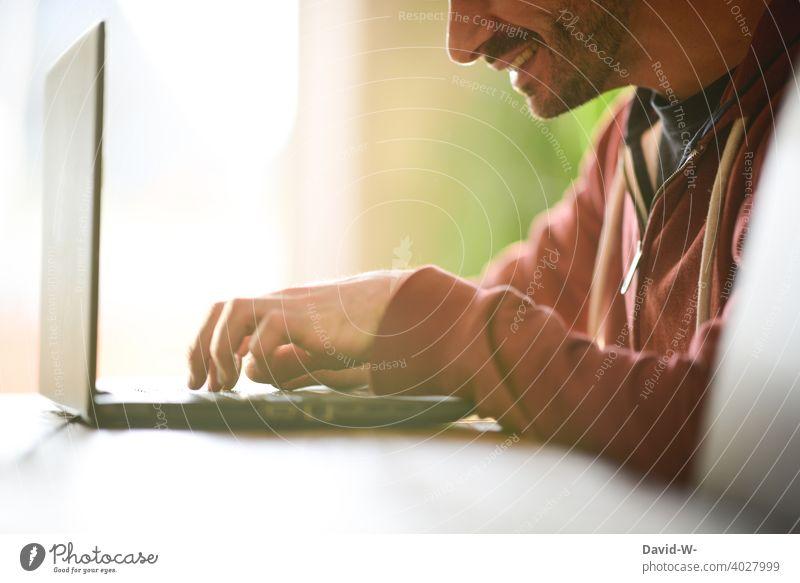 Mann arbeitet zufrieden am Laptop arbeiten Optimismus Fröhlichkeit zu Hause Homeoffice Notebook Tippen lächeln Schreibtisch