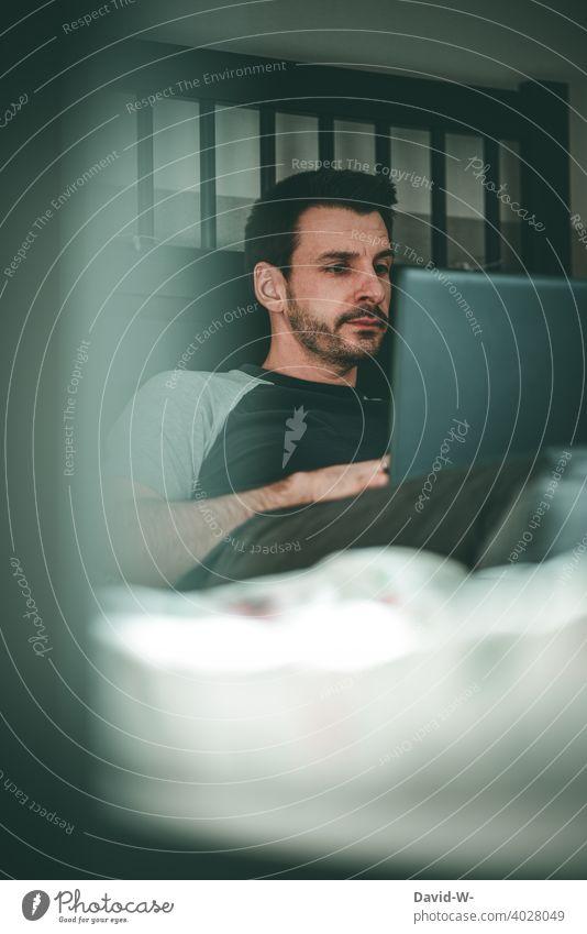 Mann liegt im Bett und benutzt einen Laptop Notebook laptop Homeoffice Internet arbeiten online Lifestyle zu Hause Quarantäne coronavirus pandemie