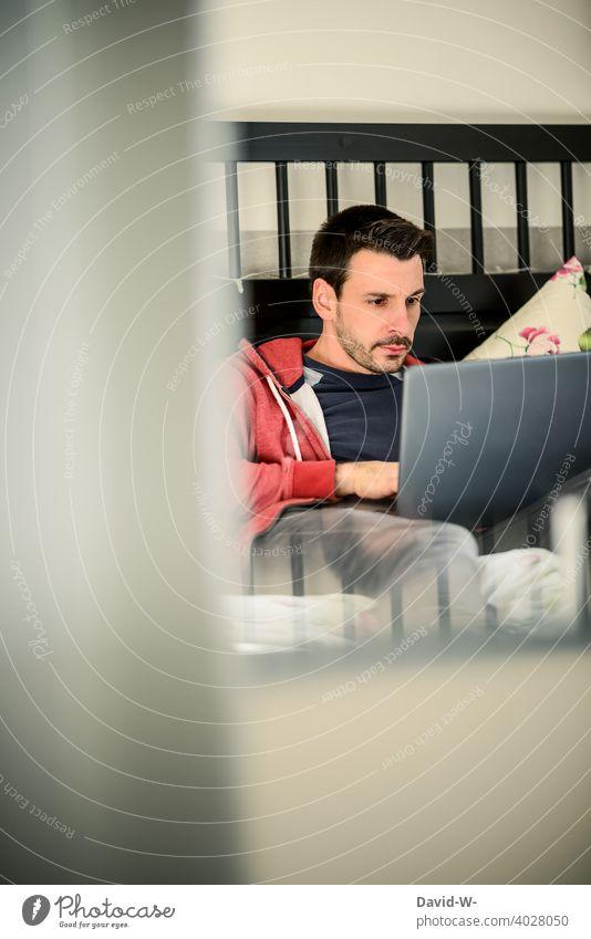Mann am Laptop im Bett arbeiten Notebook Internet Freizeit Surfen Homeoffice bequem lässig online liegen