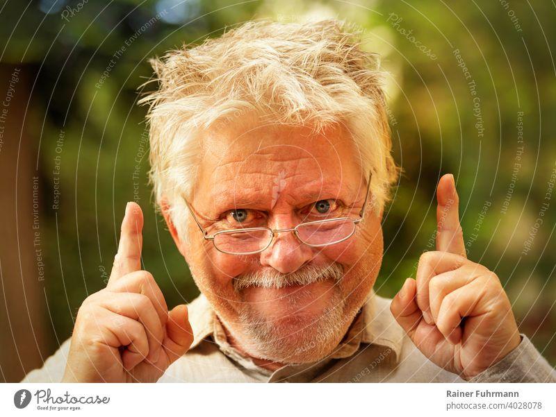 ein seltsamer Mann mit Brille hat plötzlich eine Idee Einfall Erkenntnis Einsicht Entdeckung Porträt wirr grinsen Freude Finger zeigen draußen Garten Park